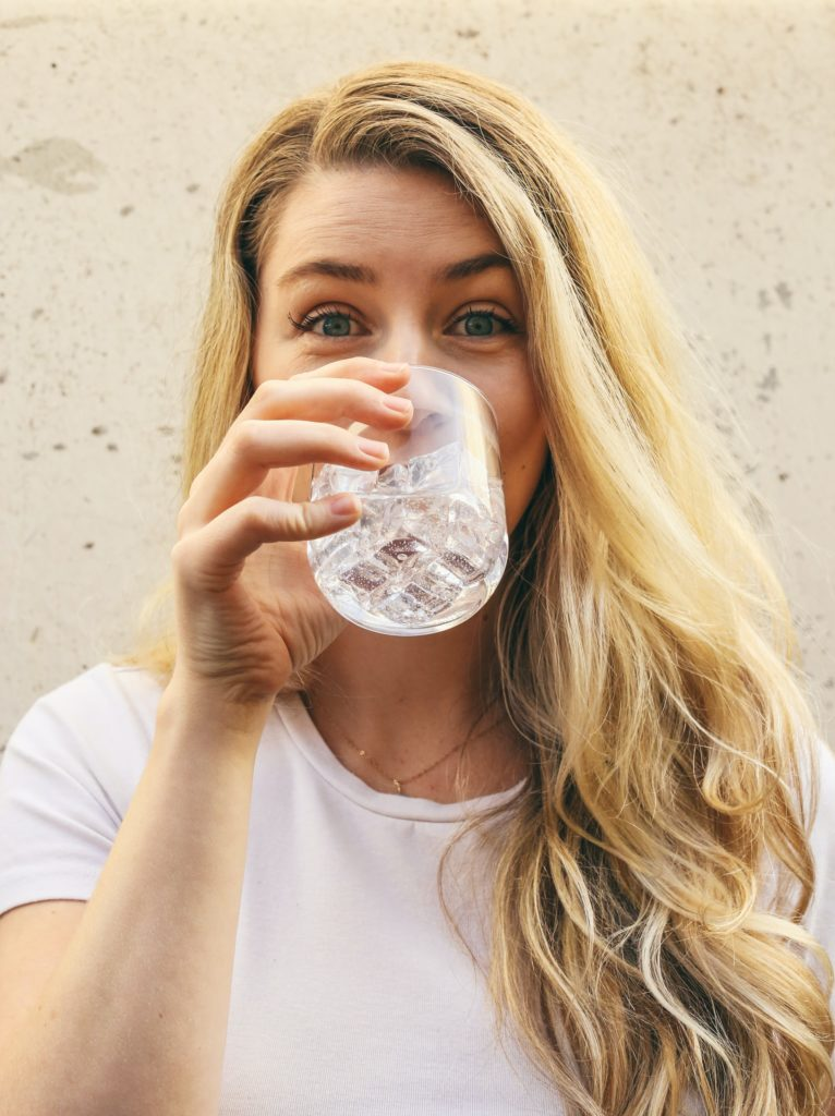 why water is important: a woman happily drinking fresh water